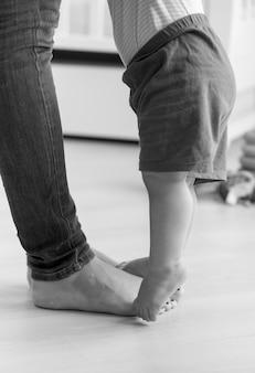 Imagem em preto e branco de close de um menino caminhando para sua mãe na sala de estar
