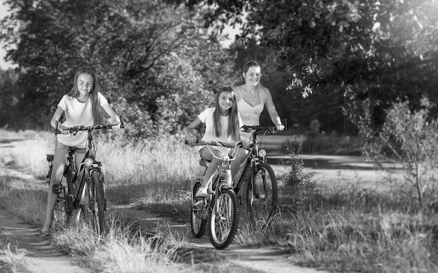 Imagem em preto e branco de família feliz pedalando em um prado
