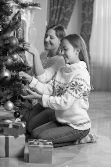 Imagem em preto e branco de feliz jovem mãe e filha sentadas no chão na sala de estar decorando a árvore de natal