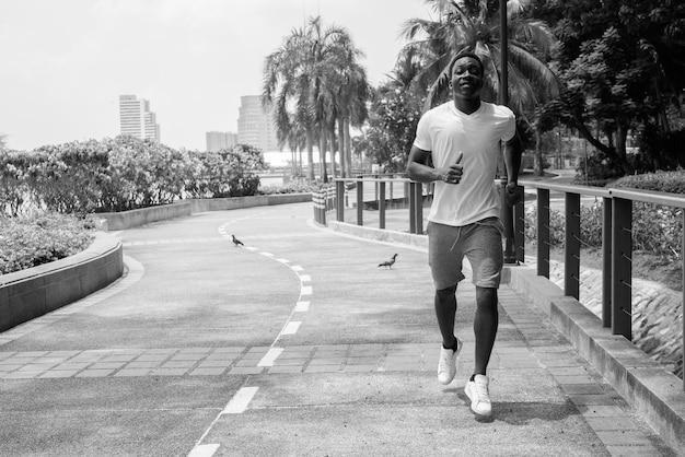 Imagem em preto e branco de jovem africano correndo ao ar livre no parque