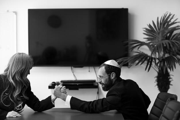 Imagem em preto e branco de parceiros de negócios israelenses competindo na arm wrestling no escritório. homem judeu de yarmulke e mulher de cabelos loiros, rostos tensos competem em uma luta de braços. feminismo, igualdade de gênero