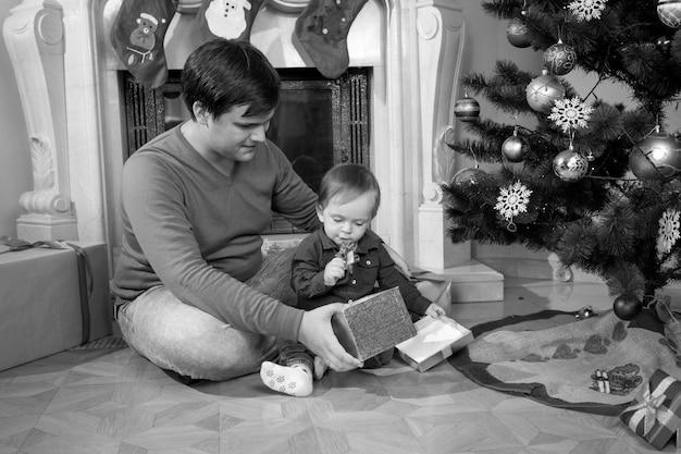 Imagem em preto e branco de um jovem pai brincando com seu filho de 1 ano ao lado da árvore de natal