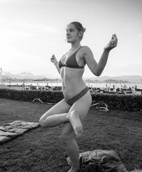 Imagem em preto e branco de uma bela jovem de biquíni praticando ioga na praia do mar