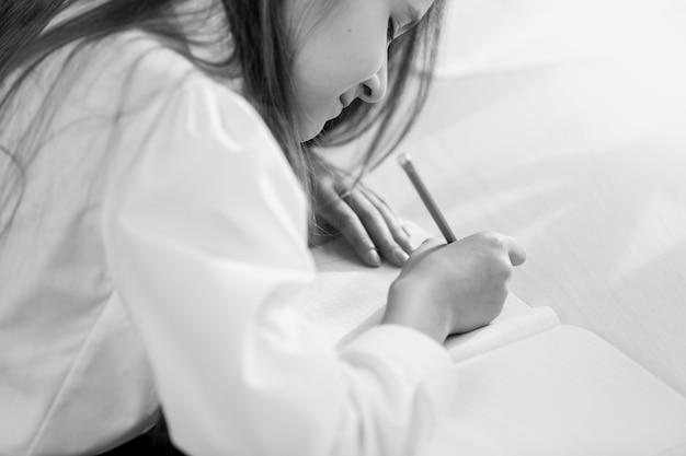 Imagem em preto e branco de uma garota fazendo o dever de casa