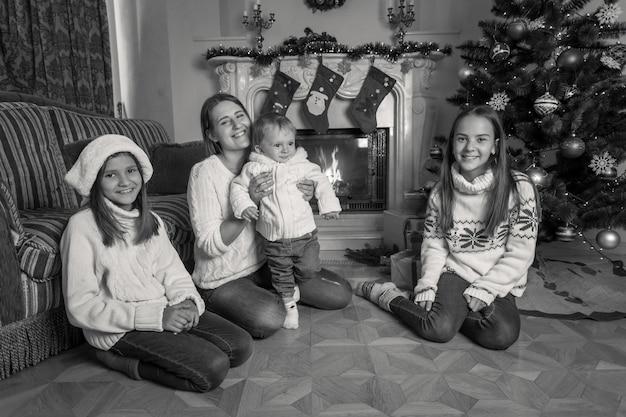 Imagem em preto e branco de uma grande família feliz sentada no chão junto à lareira no natal