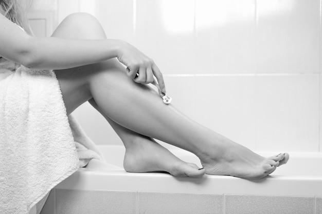 Imagem em preto e branco de uma jovem coberta com uma toalha de banho barbeando as pernas com navalha