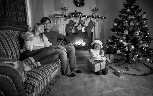 Imagem em preto e branco de uma jovem família feliz relaxando perto da lareira no natal