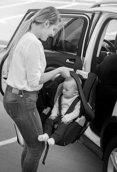 Imagem em preto e branco de uma jovem mãe colocando a cadeirinha com seu filho no carro