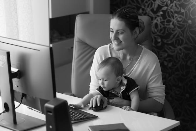 Imagem em preto e branco de uma mulher sorridente e feliz trabalhando no computador com seu filho bebê