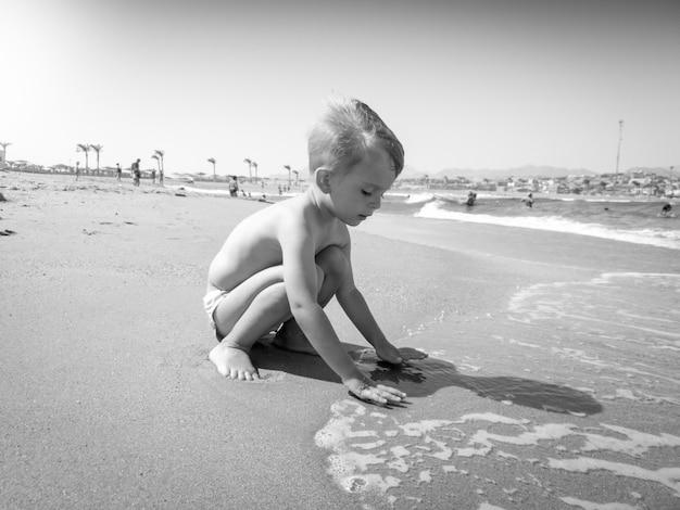 Imagem em preto e branco do adorável menino de 3 anos de idade brincando com a areia molhada e as ondas do mar na praia em um dia ensolarado. criança relaxando e se divertindo durante as férias de férias de verão.