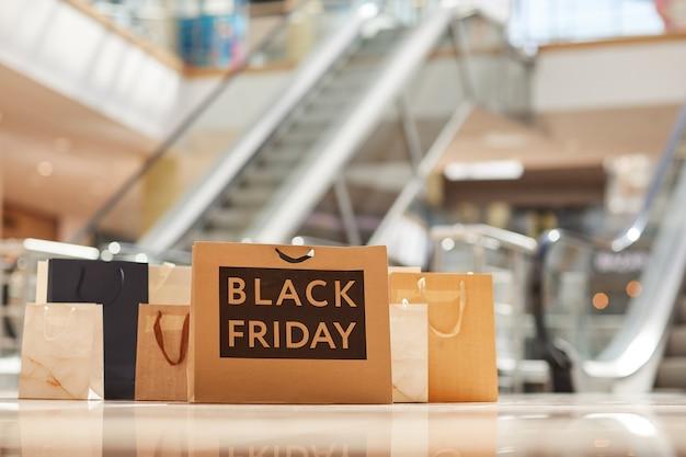 Imagem em tons quentes de sacolas de papel no chão de shopping com escada rolante na superfície, conceito de venda e sexta-feira negra, espaço de cópia
