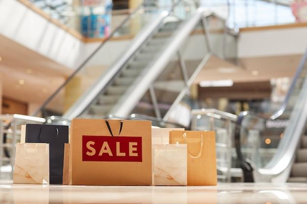 Imagem em tons quentes de sacolas de papel no chão de shopping com escada rolante na superfície, conceito de venda, espaço de cópia