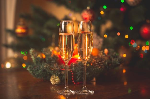 Imagem enfraquecida de duas taças de champanhe cheias na frente da guirlanda de natal com velas acesas
