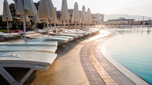 Imagem enfraquecida de espreguiçadeira vazia à beira da piscina no início da manhã. ninguém na piscina. estância balnear de verão vazia