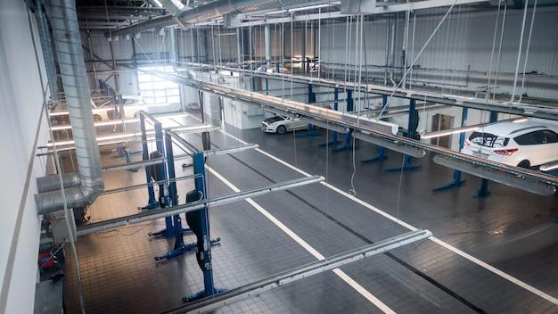 Imagem enfraquecida de oficina mecânica ou garagem com muitos elevadores hidráulicos e ferramentas para reapirar automóveis