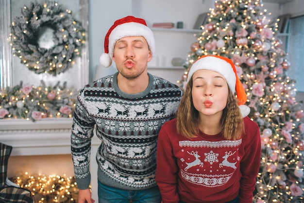 Imagem engraçada de jovem homem e mulher fica e poses. eles mantêm os olhos fechados. os lábios das pessoas estão em forma de beijo. há árvore de natal e lareira atrás deles.