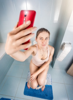 Imagem engraçada de mulher bonita fazendo selfie no telefone no banheiro