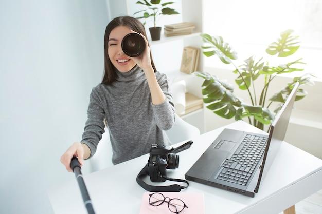 Imagem engraçada de uma mulher sentada à mesa em uma grande sala iluminada e gravando vídeo