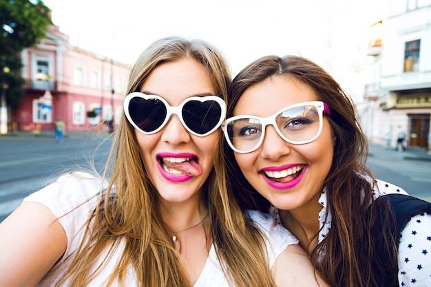 Imagem ensolarada de verão de duas irmãs melhores amigas, morenas e louras se divertindo na rua, fazendo selfie, usando óculos de sol vintage engraçados, brilhantes e elegantes com cabelos longos