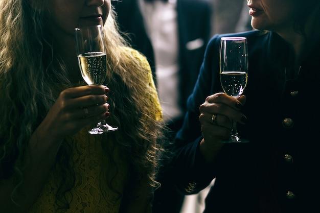 Imagem escura de mulheres falantes e flautas de champanhe em seus braços