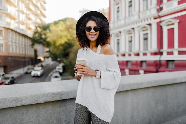 Imagem exterior do estilo de vida tonificado macio da mulher negra feliz andando na cidade de primavera com uma xícara de cappuccino ou chá quente. roupa de hipster. camisola branca tamanho grande, chapéu preto, acessórios elegantes.