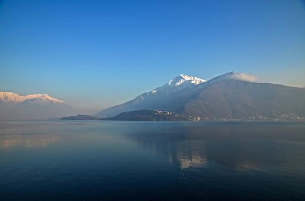 Imagem fascinante de montanhas com picos de neve refletindo na água sob o céu azul