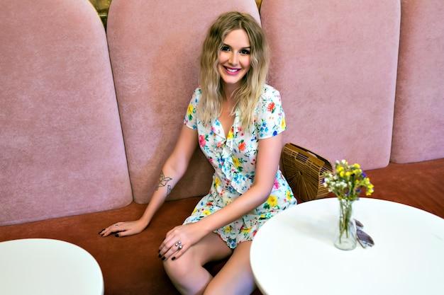 Imagem fofa de estilo de vida de uma mulher loira bonita posando, sentada, olhando para a câmera, vestido floral elegante e maquiagem brilhante