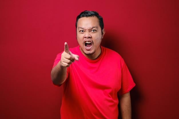 Imagem fotográfica de um homem asiático engraçado mostrando uma expressão facial cínica infeliz e zangada apontando para a frente e alertando sobre o fundo vermelho