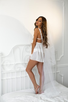 Imagem gentil em um lindo vestido branco de uma jovem com maquiagem e penteado