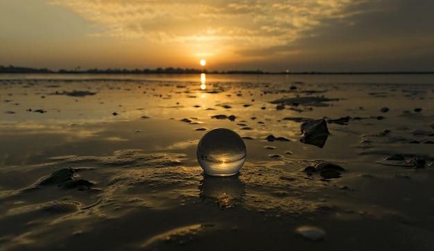 Imagem hipnotizante de uma pequena bola transparente na praia capturada durante o pôr do sol