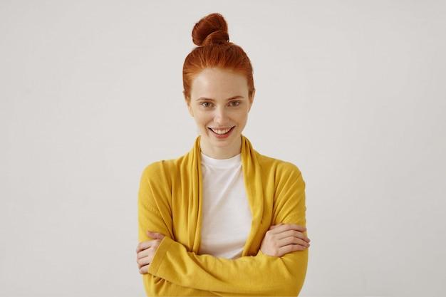 Imagem horizontal de atraente ruiva jovem confiante com cabelo elegante coque de pé contra a parede em branco branca