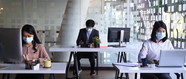 Imagem horizontal de empresários usando máscara médica, trabalhando no computador no escritório com o novo conceito de estilo de vida normal.