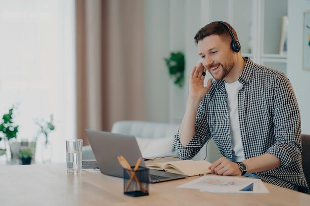 Imagem horizontal de homem alegre participa de webinar de autoaperfeiçoamento usa camisa quadriculada se comunica on-line por videochamada usa fone de ouvido e laptop estuda poses on-line no desktop