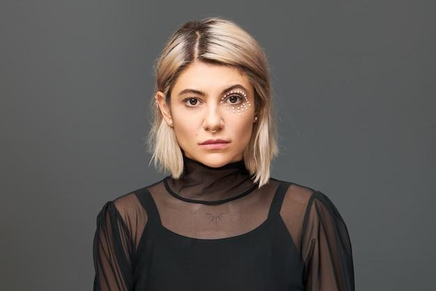 Imagem horizontal de incrível jovem mulher com penteado bob loiro e maquiagem artística com cristais brancos ao redor do olho posando isolado em uma blusa da moda, com olhar confiante