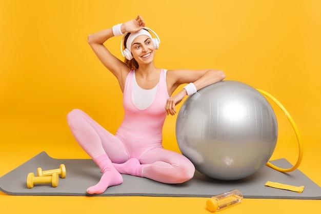 Imagem horizontal de modelo de fitness relaxado se inclina para uma bola suíça inflada sentada em karemat olhando para longe ouve música com fones de ouvido trens com halteres de bambolê leva estilo de vida esportivo isolado no amarelo