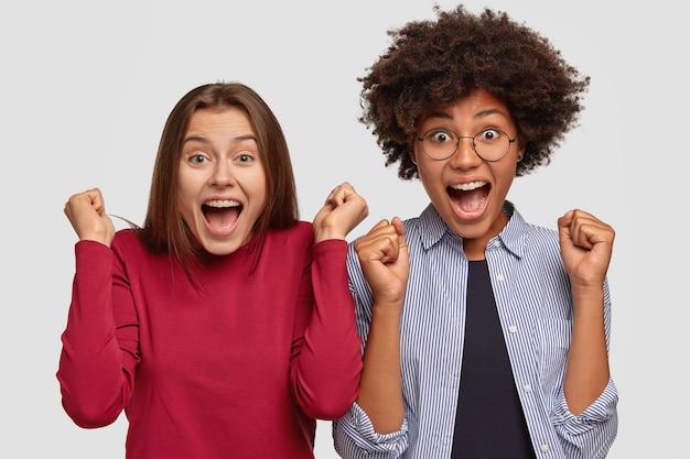 Imagem horizontal de mulheres radiantes cerrando os punhos de felicidade