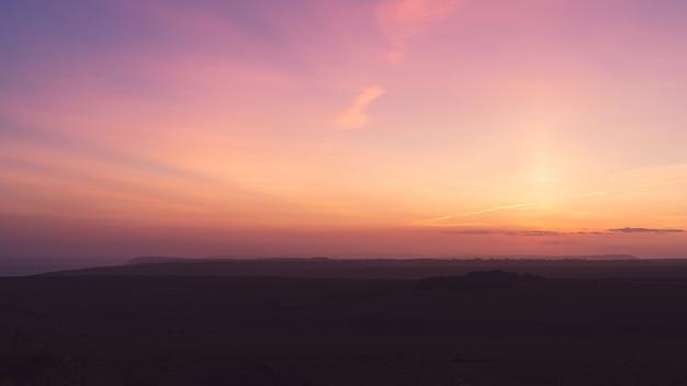 Imagem horizontal de um campo sob um céu roxo de tirar o fôlego