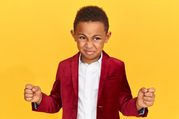 Imagem horizontal de um colegial afro-americano com raiva, mantendo os punhos cerrados, zangado com o fracasso.