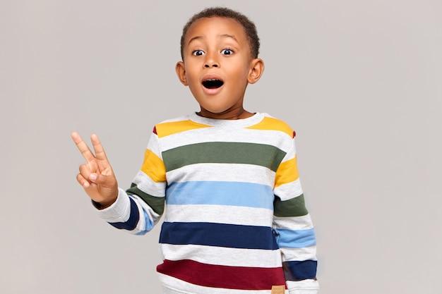 Imagem horizontal de um garoto africano animado e engraçado, mantendo a boca bem aberta, sendo surpreendido ao ver algo inesperado, fazendo um gesto de paz. criança negra emocional mostrando sinal de vitória e exclamando