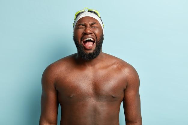 Imagem horizontal de um homem afro-americano superemotivo com um corpo forte e nu, grita emocionalmente