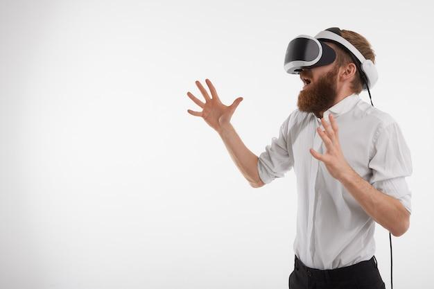 Imagem horizontal de um homem barbudo branco gritando e gesticulando emocionalmente enquanto joga videogame usando óculos de realidade virtual 3d