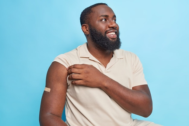 Imagem horizontal de um homem barbudo feliz por ser vacinado mostra o braço após receber a vacina engajado em uma campanha de vacinação contra o coronavírus usando camisetas casuais em poses contra a parede azul