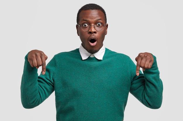 Imagem horizontal de um homem negro surpreso com os olhos saltados, aponta para baixo com os dois dedos indicadores