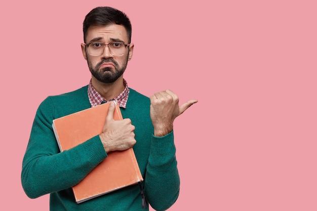 Imagem horizontal de um jovem com a barba por fazer descontente franze a testa, expressão facial infeliz, tem cerdas escuras, segura um livro vermelho grosso