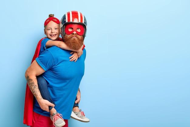 Imagem horizontal de um pai carinhoso dando carona para uma criança pequena
