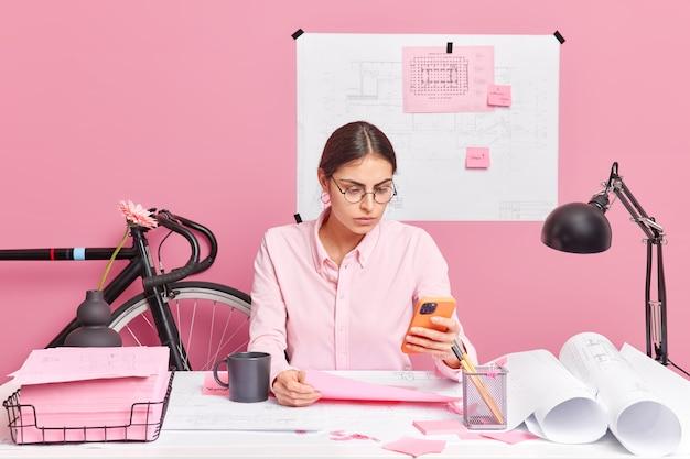 Imagem horizontal de uma aluna séria trabalhando em um projeto arquitetônico concentrado em poses de exibição de smartphone em um esboço de análise de espaço de coworking envolvido no processo de trabalho torna o planejamento