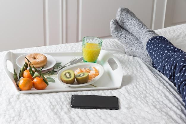 Imagem horizontal de uma bandeja com um café da manhã na cama ao lado de um celular preto e as pernas de uma mulher de pijama azul e meias cinza em uma cama com colcha branca