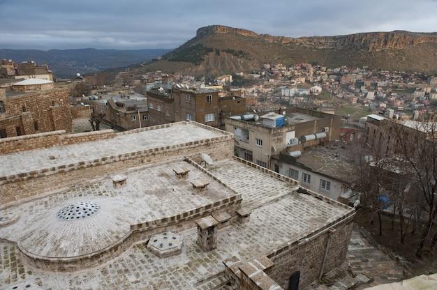 Imagem horizontal de uma cidade no sopé de uma colina com edifícios antigos
