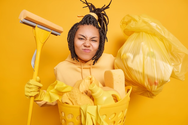 Imagem horizontal de uma dona de casa ocupada com um sorriso afetado e uma careta