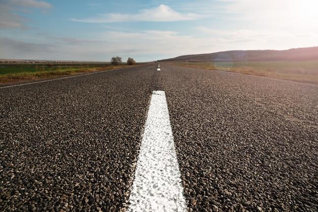 Imagem horizontal de uma estrada reta longa e vazia